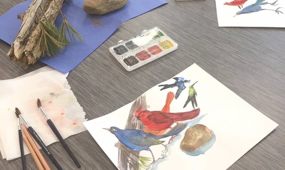 Paint palete, a paintbrush, and a painting of birds sits on a table in the Art Studio at The Ambassador