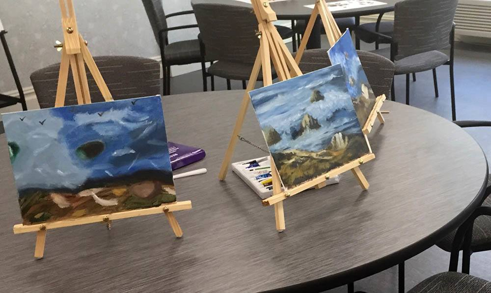 Paintings sit on small tabletop easels in the Art Studio at The Ambassador