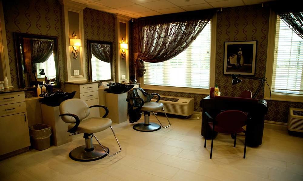 Hairdresser chairs and dryers set by sinks in the Beauty Salon at The Ambassador