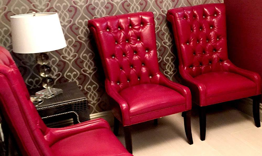 Red leather chairs set up in the waiting area of the Beauty Salon at The Ambassador
