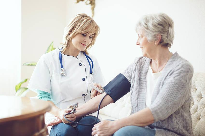 A nurse checks a residents blood pressure