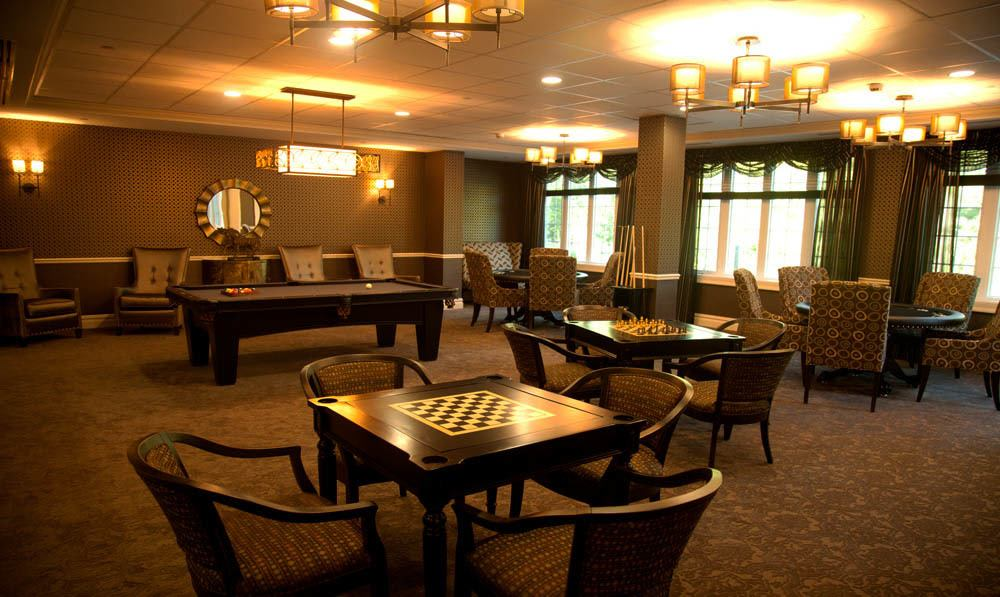 Chesse tables, a pool tables and cues set amongst comfortable chairs and tables in the Club Room at The Ambassador