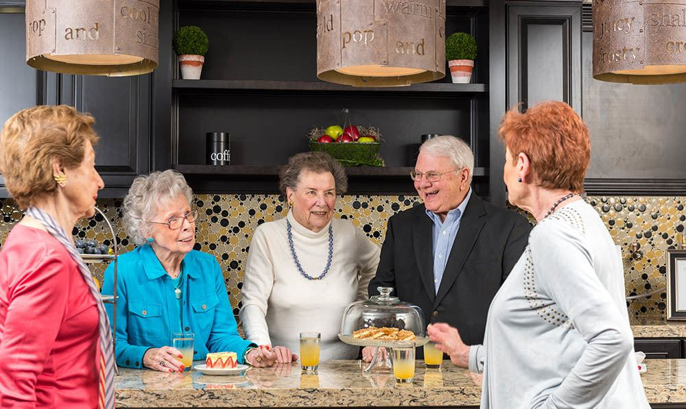 A group of residents drinking coffee and chatting in the Five Corners Bistro at The Ambassador