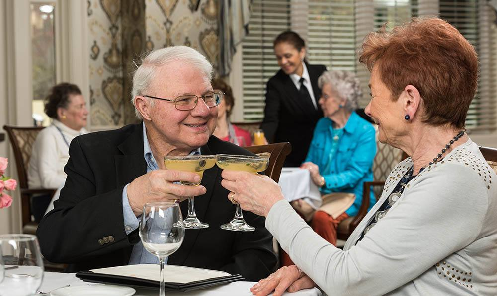 Lady and gentleman enjoying drinks at a table in the Heathcote Dining Room at The Ambassador
