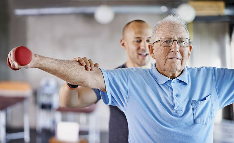 Man lifting arms up with support of personal trainer