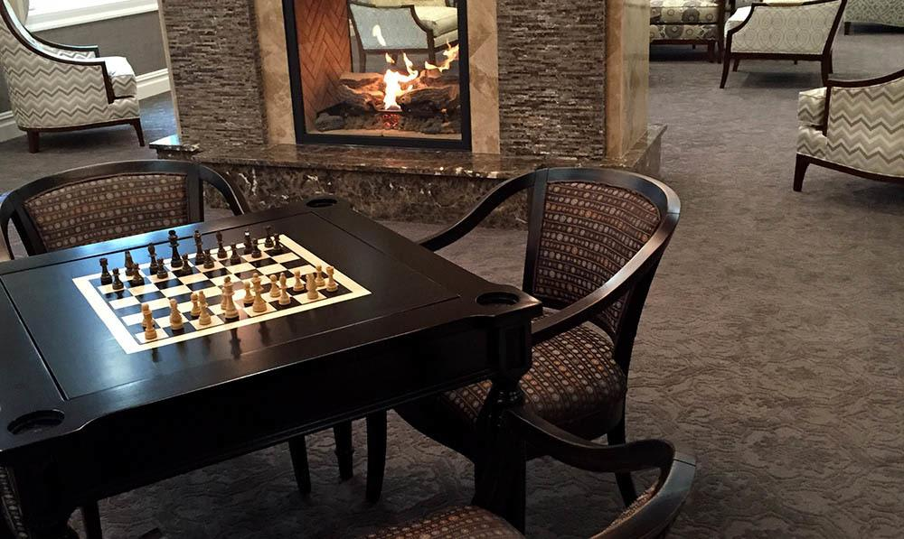 A game of chess set up on a chess board built into a table at the Club Room at The Ambassador