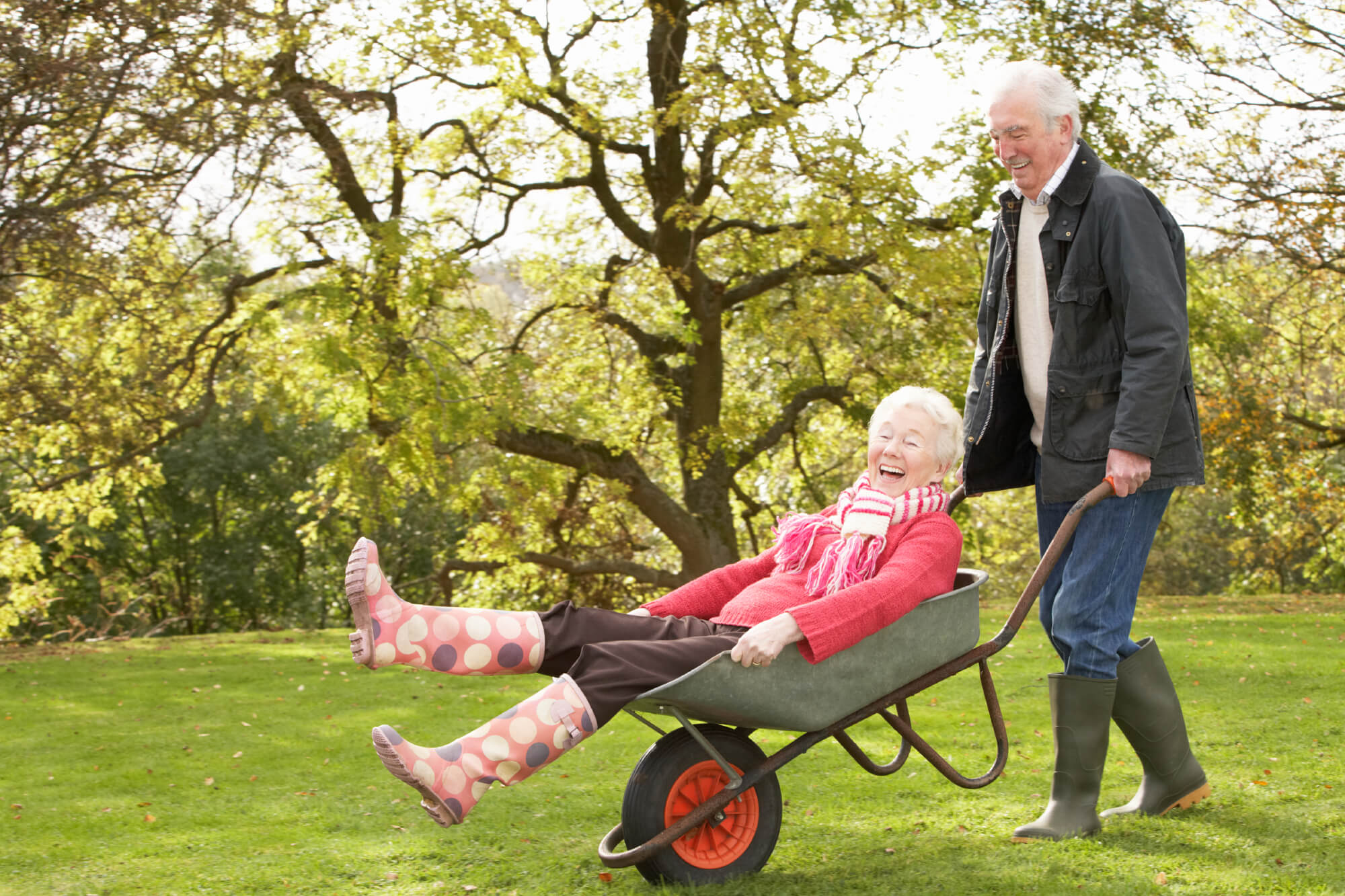 Two residents enjoying the gandens outside as one playfully pushes another in a wheelbarrow
