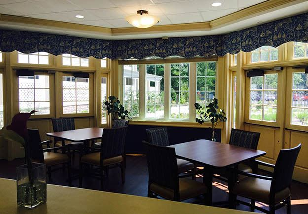 Tables by the windows overlooking the garden by the Five Corners Bistro at The Ambassador