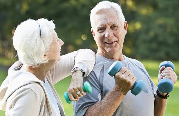 Man and woman walking carrying light dumbbells